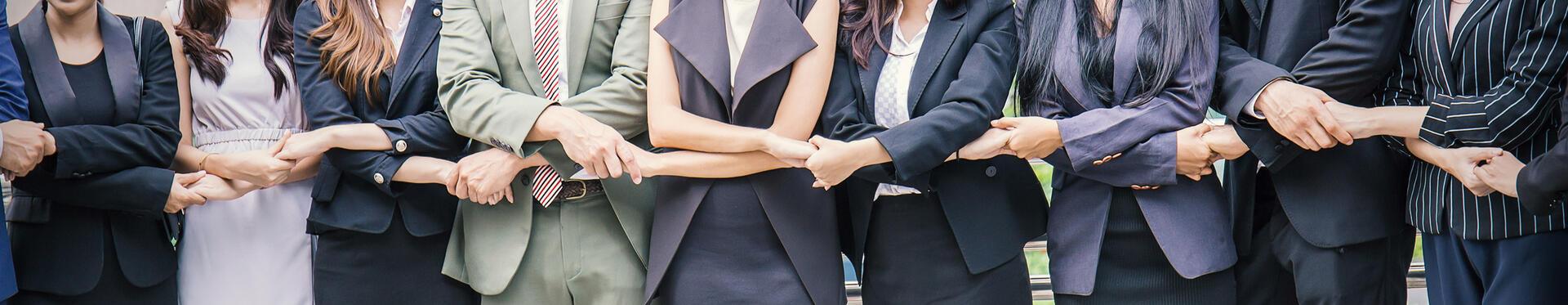 Ryhmä ihmisiä vierekkäin, jotka pitävät toisiaan kädestä kiinni